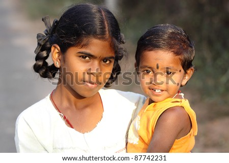 Indian girl with little boy in outdoor background.