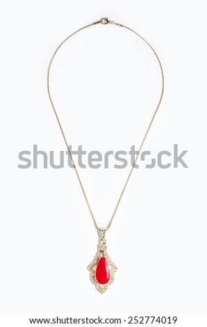 Indian gold pendant with red gem on a white background