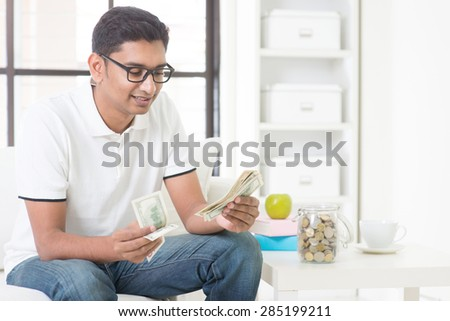 Indian guy counting money and smile at home. Asian man holding cash indoor. - stock photo