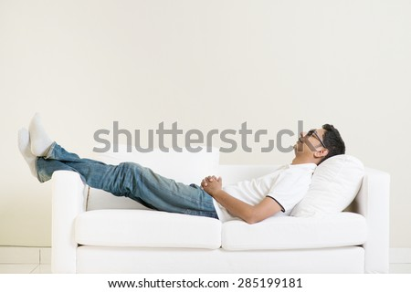 Indian guy daydreaming and rest at home. Asian man relaxed and sleep on sofa indoor. Handsome male model. - stock photo