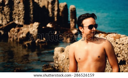 Indian handsome happy young man getting out of water with sunglasses under blue sky - stock photo