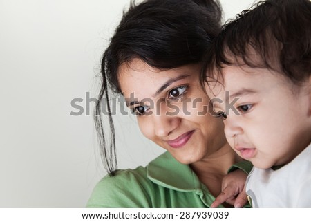 Indian happy mother and baby smiling looking at others over gray background