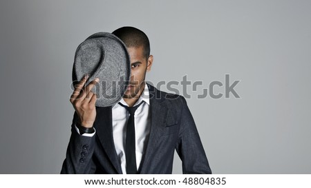 Indian high fashion model covers half his face with a fedora - stock photo