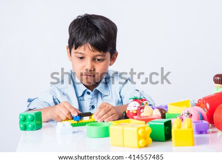 indian kid playing with block toys, asian small boy playing indoor games, colorful plastic block toys, making toy house, over white background, indian small boy playing blocks - stock photo