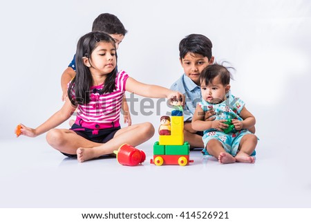 indian kids playing with block toys, asian small kids playing indoor games, colorful plastic block toys, making toy house, over white background, indian small girl and indian small boy playing blocks - stock photo