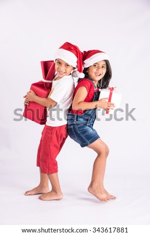indian kids with christmas gifts, asian kids with christmas gifts, isolated on white background, closeup - stock photo
