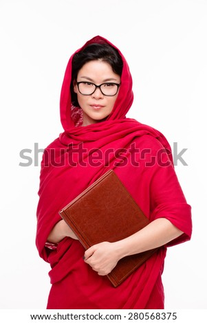 Indian lady dressed in traditional red-coloured sari and with glasses on keeps the register in her hands. Now she is ready for her classes. - stock photo