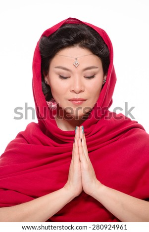 Indian lady dressed in traditional red-coloured sari is looking at her clasped hands. She wants to concentrate on her pray. - stock photo