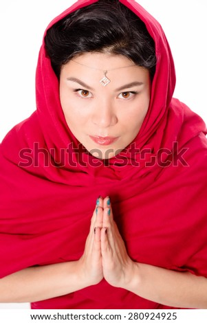 Indian lady dressed in traditional red-coloured sari with her hands clasped is looking at you. She is begging you to help her when she will be praying.