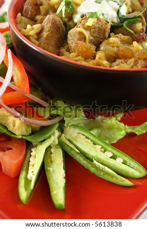 Indian lamb biryani with sultanas and yoghurt and a side salad. - stock photo