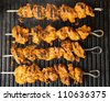 Indian lamb tikka kebabs cooking on hot griddle plate. - stock photo