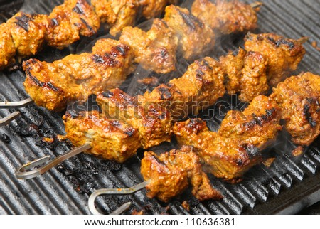 Indian lamb tikka kebabs cooking on hot griddle plate. Shallow DoF, focus on centre. - stock photo