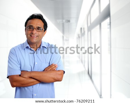 indian latin businessman glasses blue shirt in modern office corridor [Photo Illustration] - stock photo