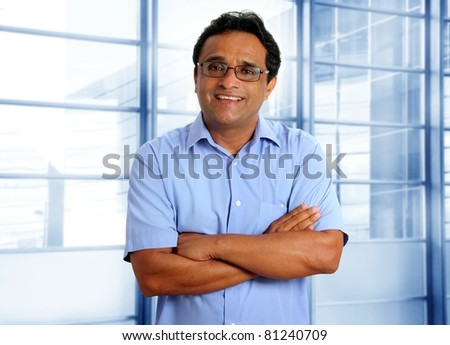 indian latin businessman with glasses and blue shirt in modern office [Photo Illustration] - stock photo