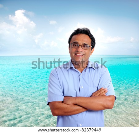 Indian latin tourist man spending his vacation in a perfect turquoise beach  [Photo Illustration] - stock photo