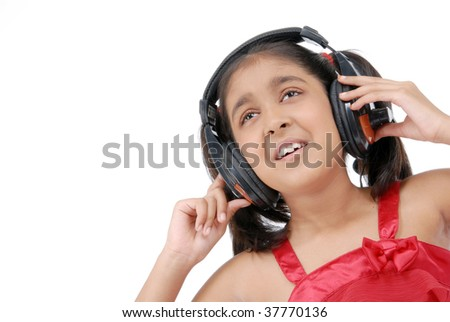 Indian little pretty girl listening music in headphone