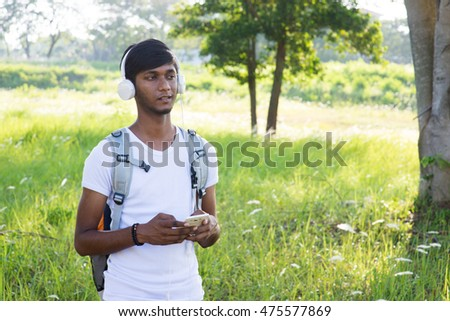 indian male college student listening to music outdoor