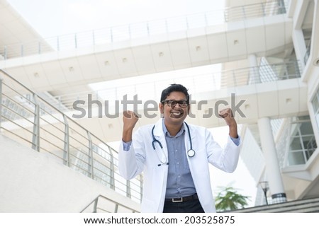 indian male doctor celebrating success in outdoor hospital - stock photo
