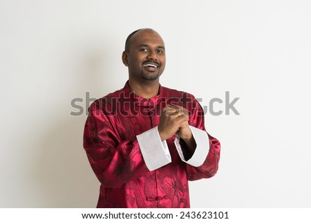 indian male with chinese new year clothes giving greetings