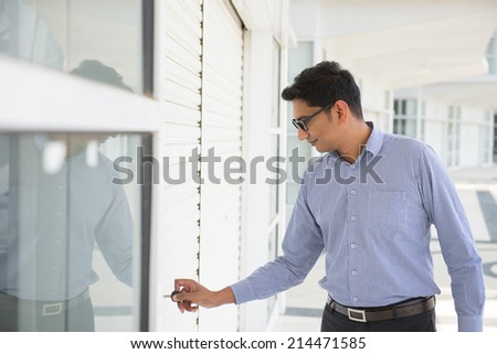 Indian man checking on new office to let, holding newspaper and calling on phone.