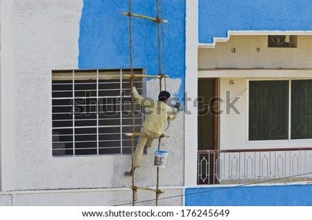 Indian man coloring blue color on wall hanging on a rope ladder - stock photo