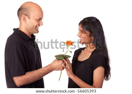 Indian man giving yellow rose to an attractive Indian woman.