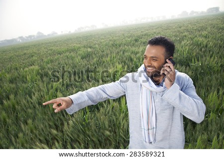 Indian man in a field pointing away while on a call - stock photo