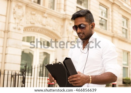 indian man in the street using an tablet