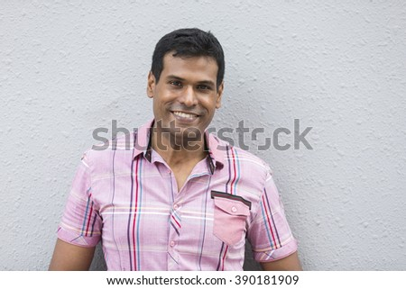 Indian man leaning on a grey wall. Handsome young Asian man leaning against a grey wall and looking at the camera - stock photo