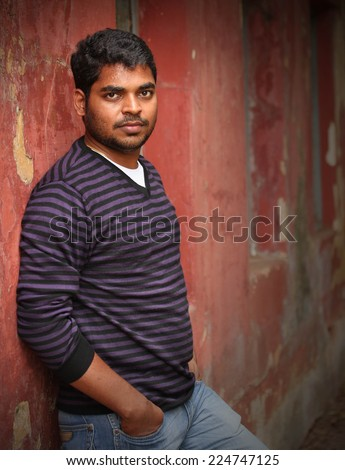 indian man leaning on a wall causally, relaxed, looking at camera. The person can also represent a latin or a mexican businessman - stock photo