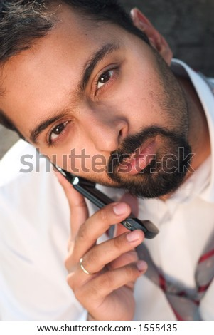 Indian man on a mobile phone. Focus on the right eye.