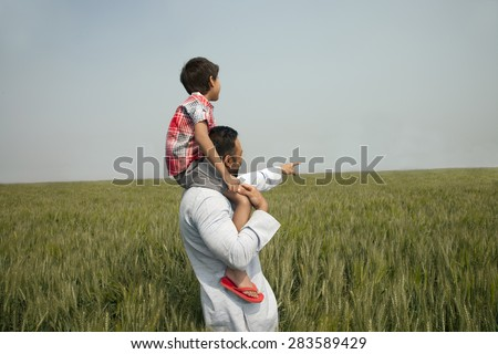 Indian man pointing at something while carrying son on shoulders - stock photo
