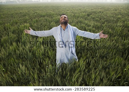 Indian man standing in field with arms out - stock photo