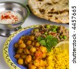 Indian meal of keema matar, masala channa, lemon rice, naan bread and yoghourt, which is minced lamb with peas, spicy chickpeas, yellow rice, nan bread and yogurt. Focus on mint. - stock photo