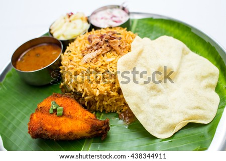 Indian meal with fish and fried rice on banana leaf tray - stock photo