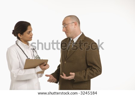 Indian mid adult woman doctor talking with man in business suit. - stock photo