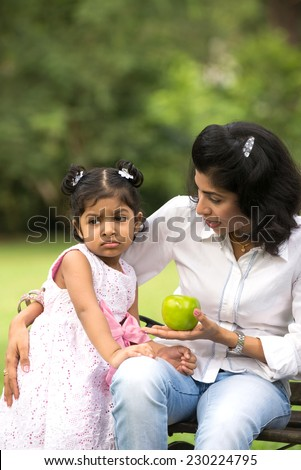Indian mother and child eating healthy outdoor - stock photo