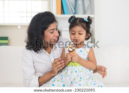 indian mother and child enjoying ice cream indoor - stock photo