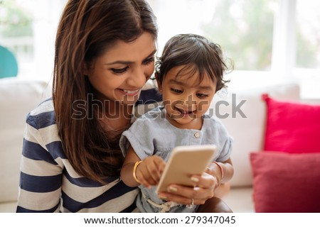 Indian mother and child playing game on the smartphone - stock photo