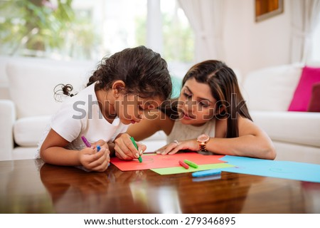 Indian mother and daughter drawing with crayons - stock photo