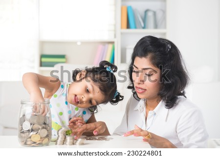 indian Mother and daughter putting coins into bottle, saving plan  - stock photo