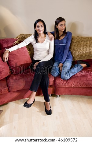 Indian mother and mixed-race teenage daughter sitting together on sofa - stock photo