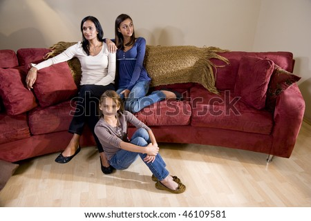 Indian mother and two mixed-race daughters sitting together at home in living room - stock photo