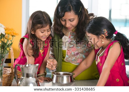 indian mother cooking with her daughters at kitchen - stock photo