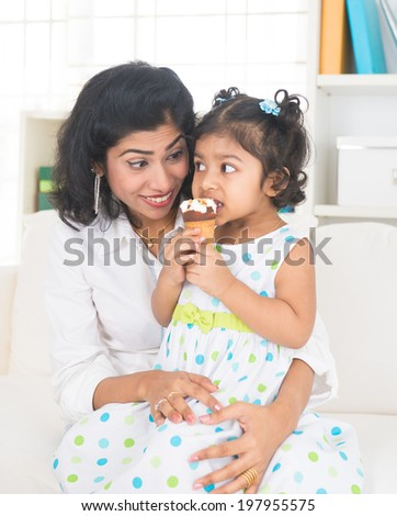 indian mother enjoying ice cream with her daughter on lifestyle background - stock photo