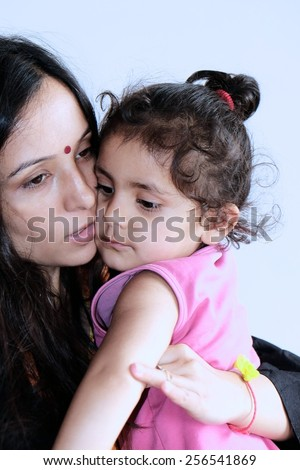 Indian mother holding her kid in arms. - stock photo