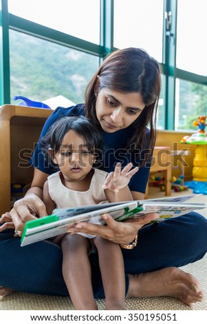 Indian mother reading book with her daughter - stock photo