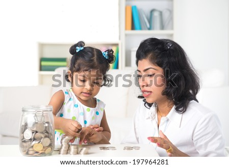 indian mother teaching daughter on financial planning indoor - stock photo