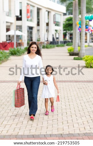 Indian mother walking with her daughter along the street - stock photo