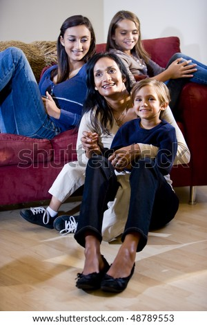 Indian mother with three mixed-race children relaxing on living room sofa - stock photo